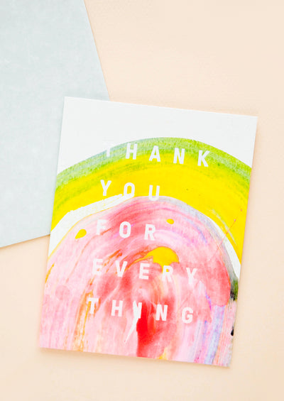 "A greeting card featuring a sweep of multicolored paint in yellow and pink with white text reading ""thank you for everything."""