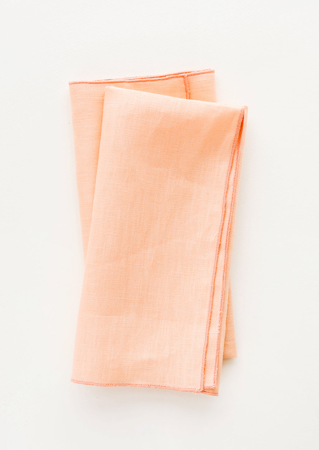 Peach: Pair of folded linen napkins in peach with tonal trim