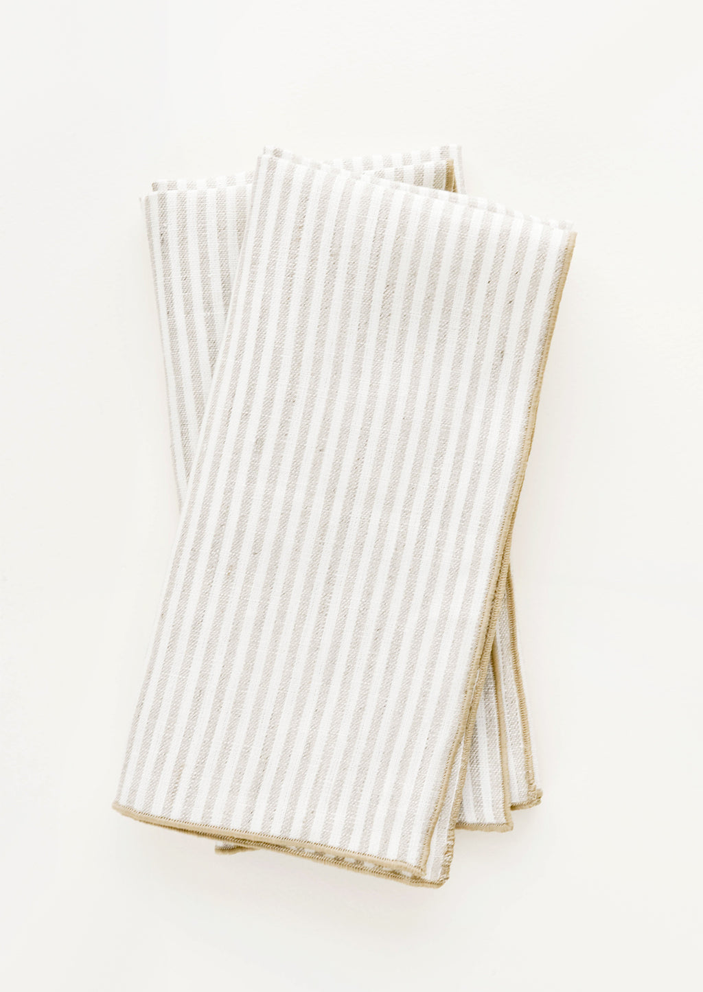 Flax Stripe: Pair of ivory folded Linen Napkins with light brown vertical stripe.