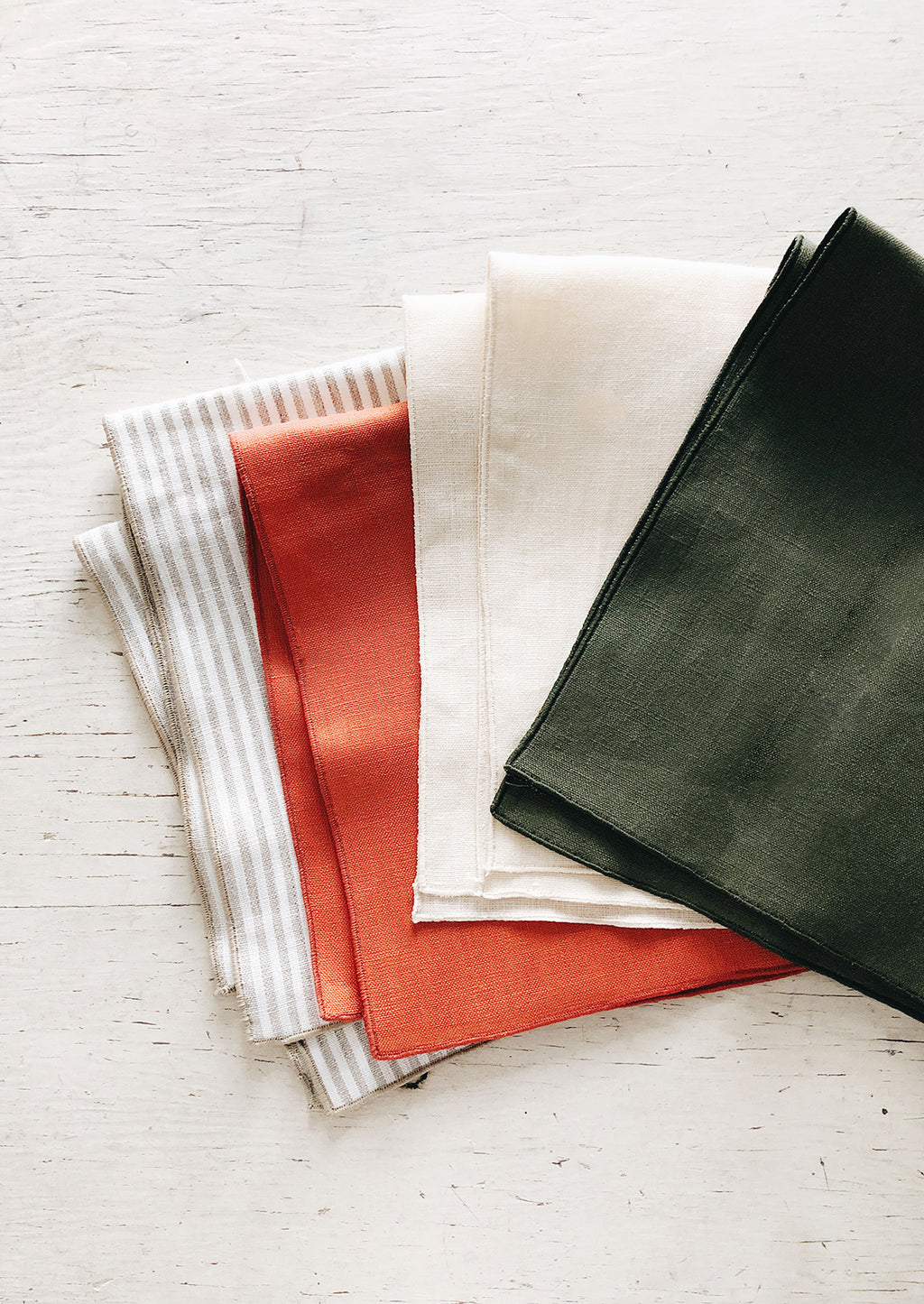 Tomato: Linen Napkins splayed out in an array of colors.