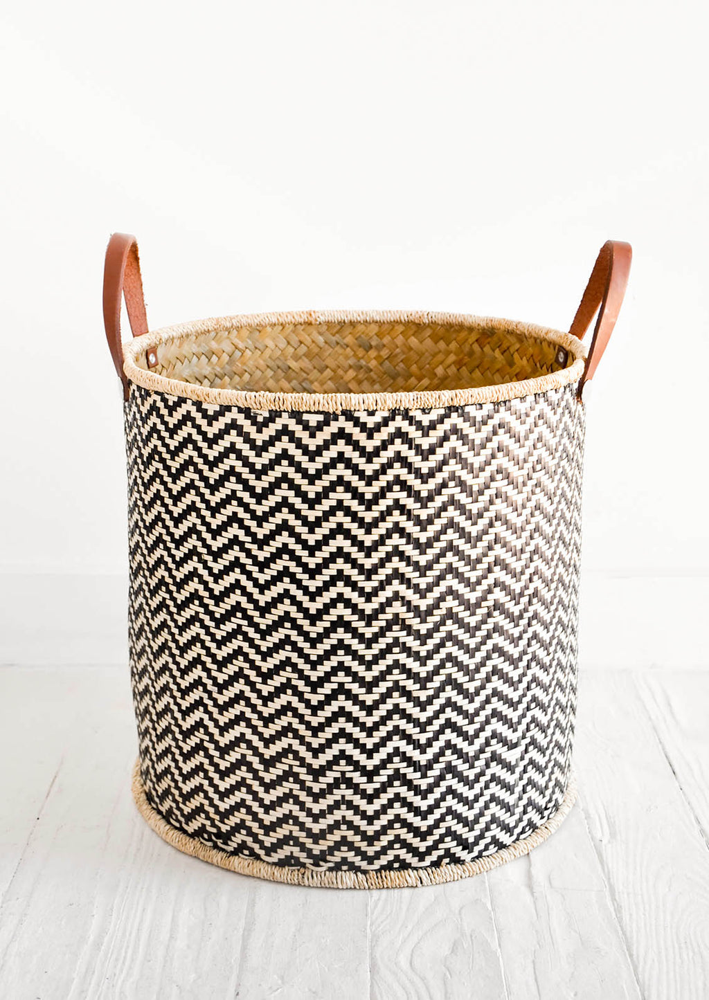 1: Round storage bin in natural material with allover black zigzag pattern and leather handles