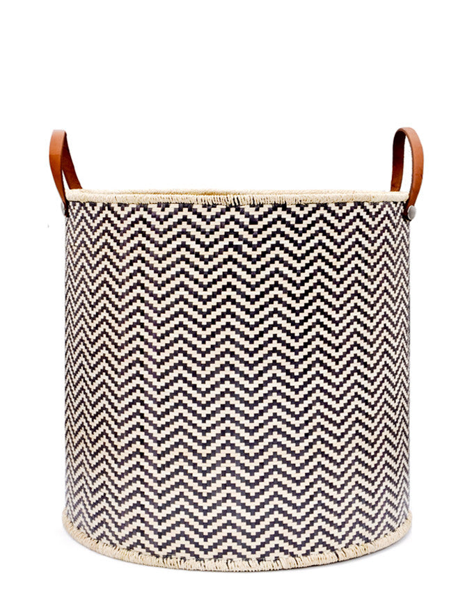 Round storage bin in natural material with allover black zigzag pattern and leather handles
