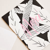 "2: Notecard with black and white palm leaves decoration and the word ""Merci"" in pink, and white envelope."