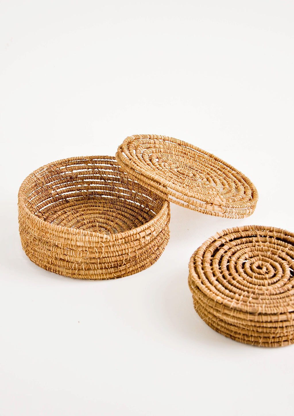 1: Small, round and shallow baskets made from brown palm fiber with removable lids.