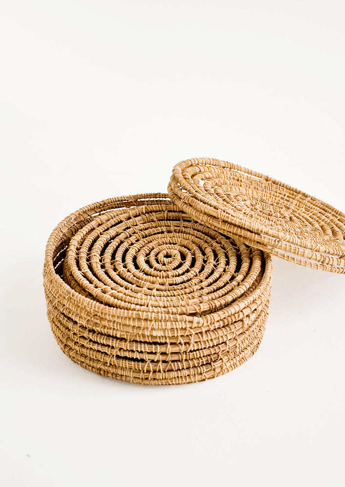 3: Small, round and shallow baskets made from brown palm fiber with removable lids, nested in side of each other when not in use.