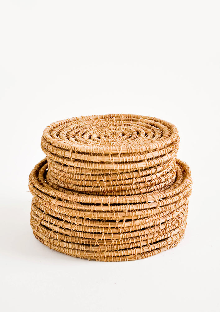 2: A stack of two small, round and shallow baskets made from brown palm fiber with lids.