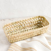 Narrow: A shallow, narrow storage basket made from dried palm leaf.