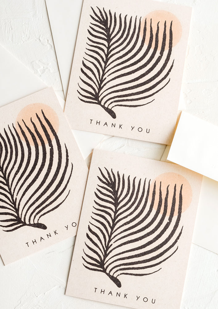 1: Three identical thank you cards with image of palm leaf and sun on front.