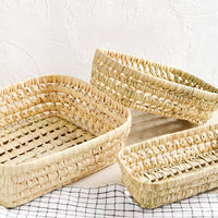 2: Three shallow baskets woven from natural dried palm leaf.