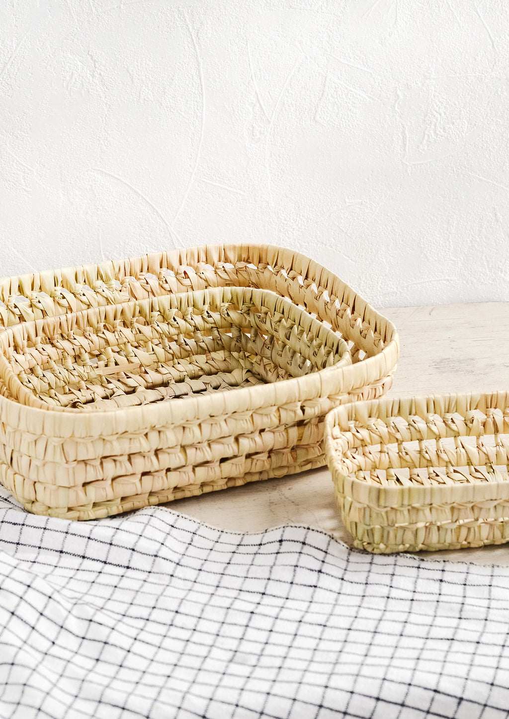 3: A collection of shallow nesting baskets made from palm leaf.