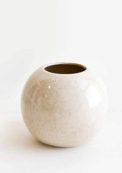 Round, spherical planter with wide opening at top. Glossy, neutral glaze with light speckles.