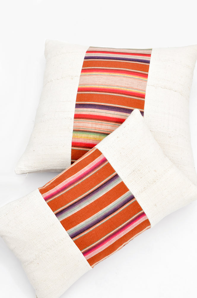 1: Square and rectangular throw pillows with plain ivory left and right sides, and striped center panel in earth tones.