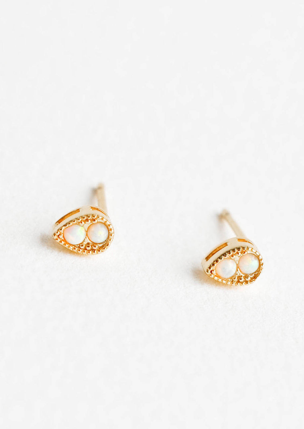 Teardrop: Teardrop shaped stud earrings in gold finish, with two small round opal stones inset.