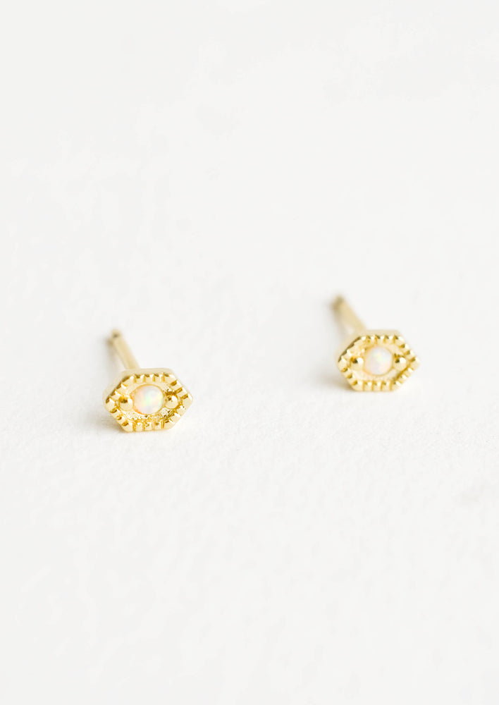 Hexagon shaped stud earrings in gold finish, with small round opal stone inset.