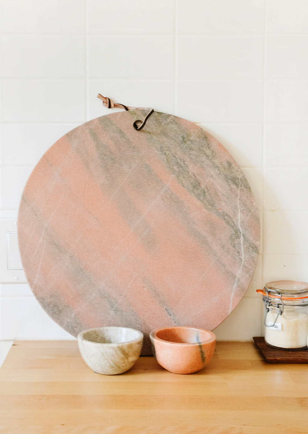 3: Pink and tan marble serving platter and prep bowls on a kitchen counter