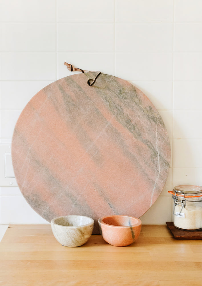4: Pink and tan marble serving platter and prep bowls on a kitchen counter