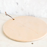 2: Round, peach colored marble serving platter sitting atop a rustic table.