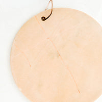 1: Round marble serving platter in peach colored marble with brown leather tie at top