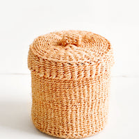 1: Small, round woven basket with matching lid made from peach-colored sisal