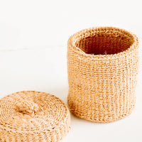 2: Small, round woven basket with matching lid made from peach-colored sisal
