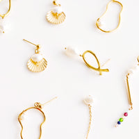 4: Product shot showing multiple styles and shapes of brass earrings with pearls.