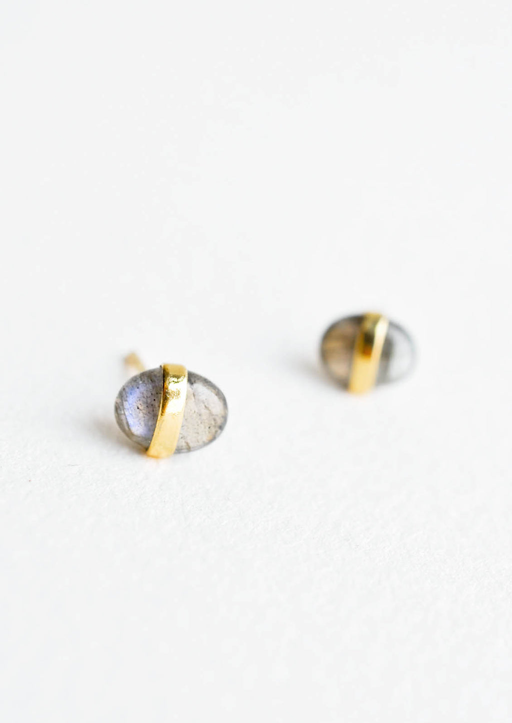 1: Oval-shaped, pebble-like stud earrings in iridescent labradorite with golden band wrapped around middle.