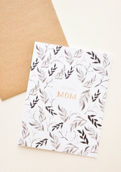 "Brown paper envelope and white greeting card with black floral motif surrounding the words ""to you, mom"" in gold foil."