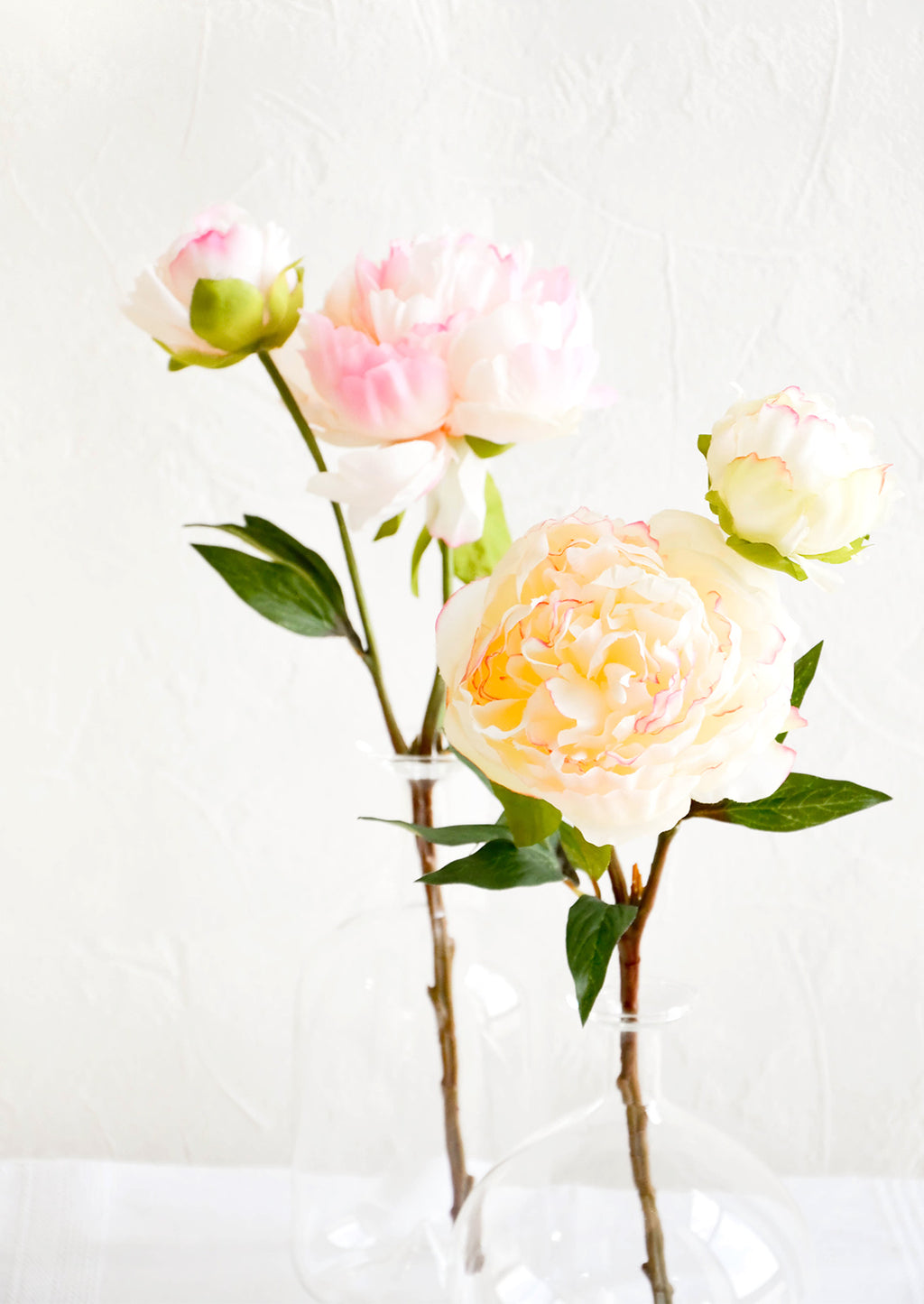2: Realistic faux peony flowers in white and pink, displayed in glass vases
