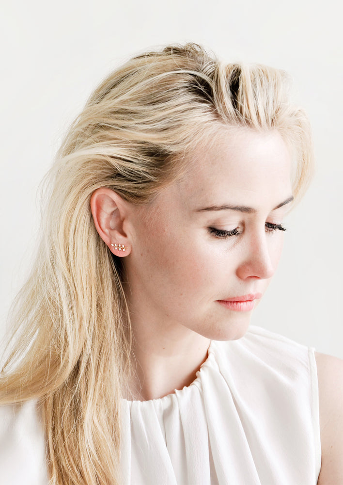 2: Model wearing leaf shaped stud earrings.