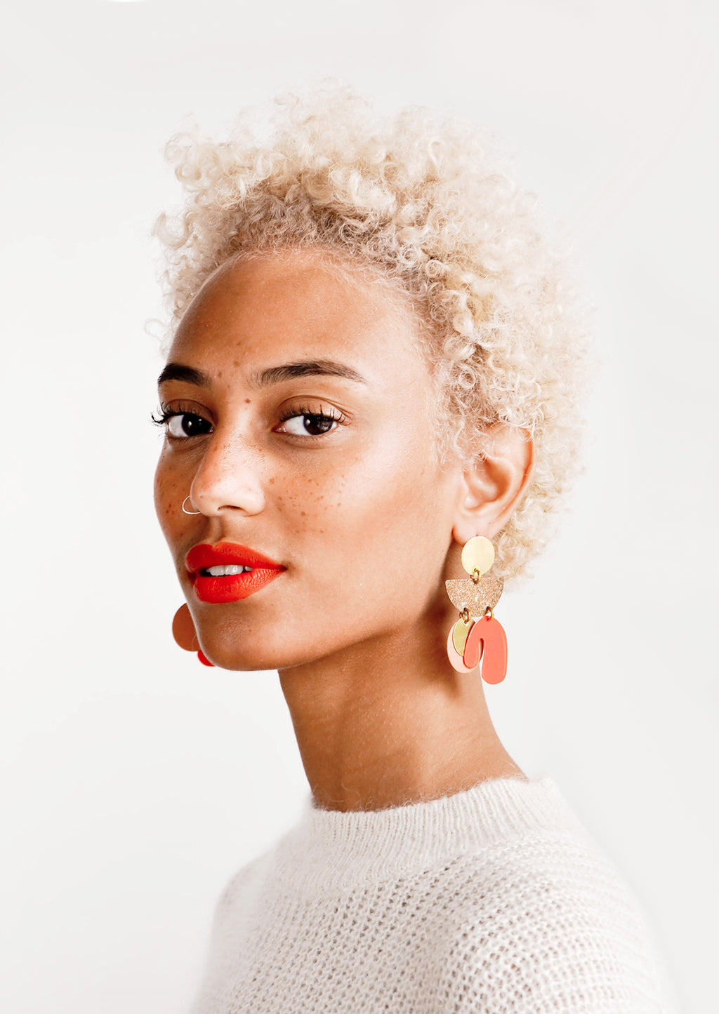 2: Model wears orange and gold earrings with white top.