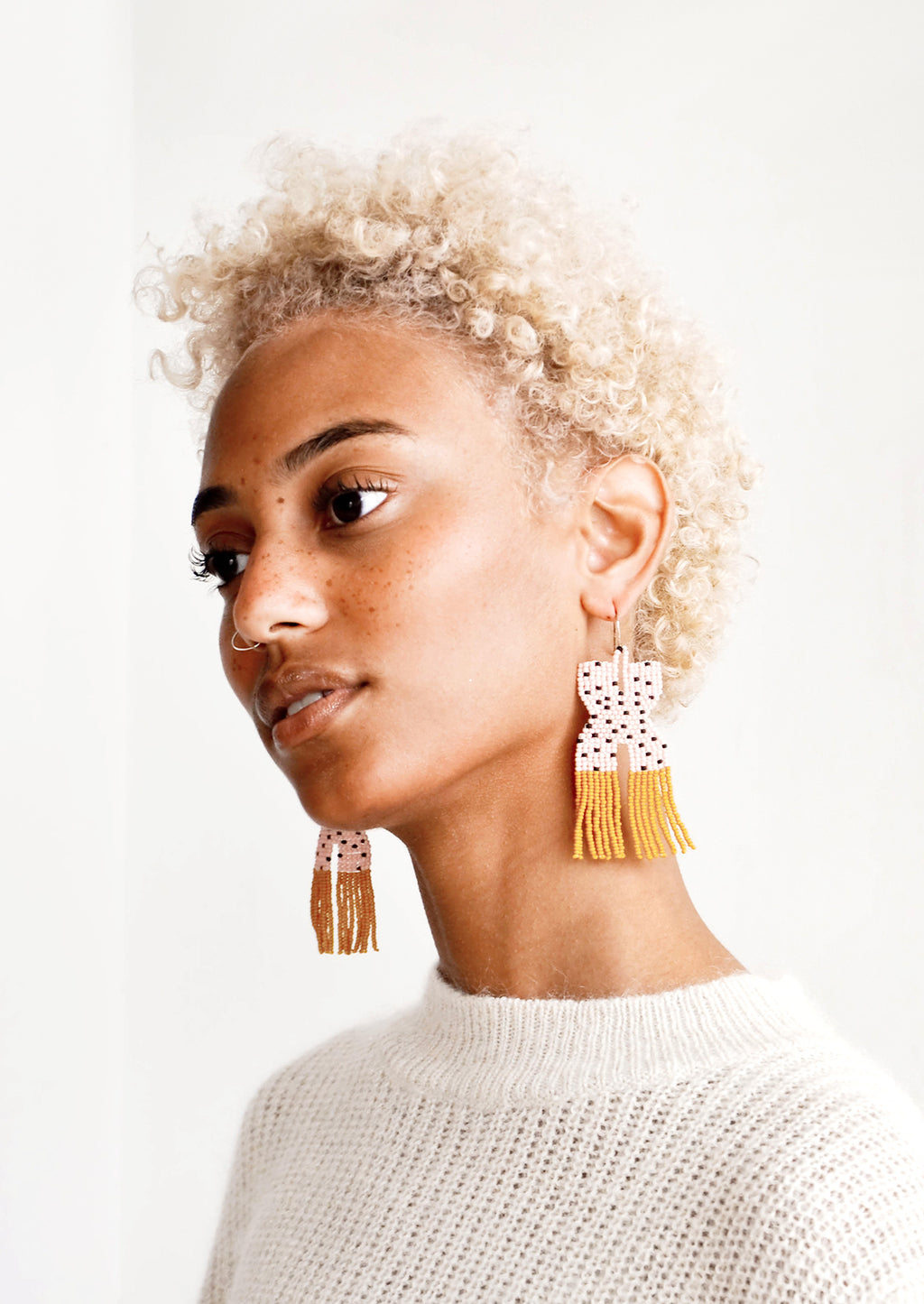 2: Model wears pink and yellow fringe beaded earrings.