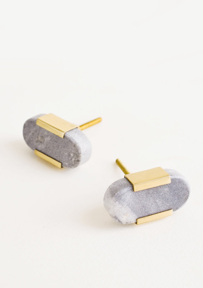 Grey Marble: Pill shaped cabinet knob made in solid grey marble with brass accents