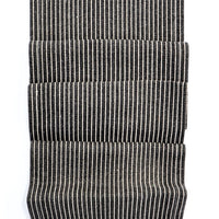 Charcoal: Jute table runner in charcoal with white pinstripes. Frayed ends with orange stitching.
