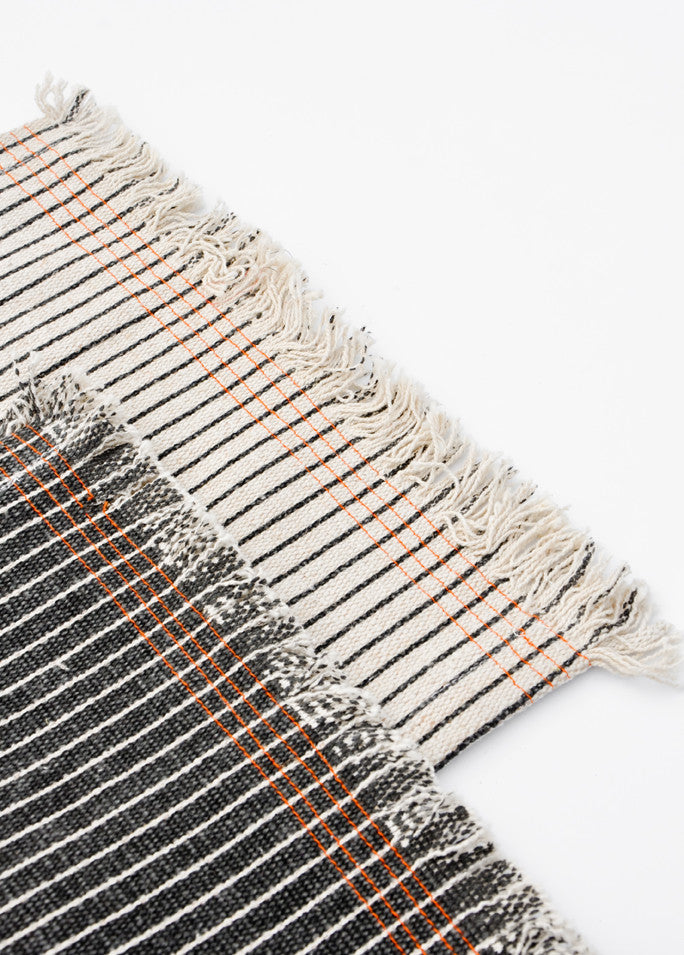 1: Table runners with frayed edges. Black and white pinstripe with orange stitching detail.