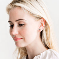 4: Model wears stud earrings with ivory blouse