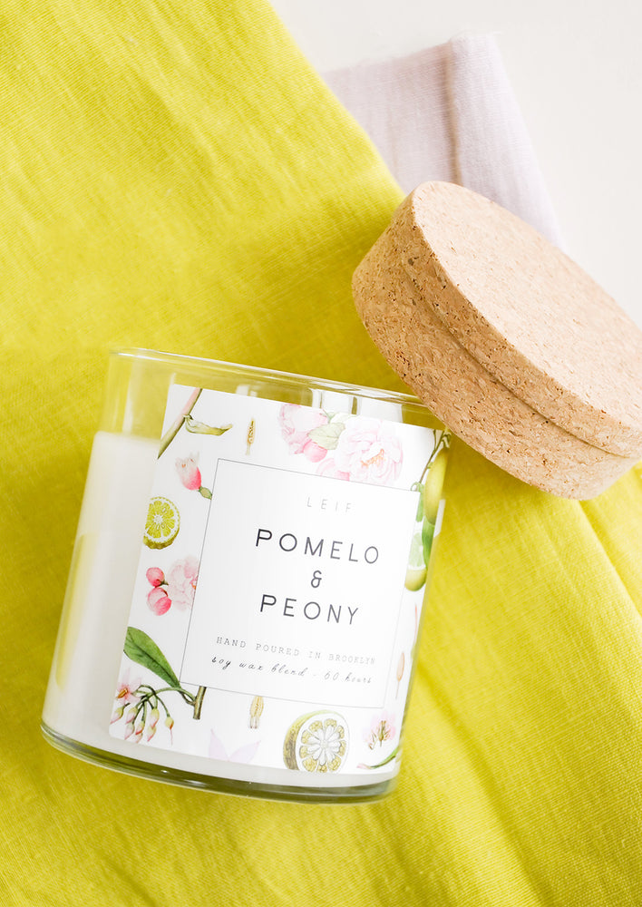 Pomelo & Peony: A glass candle with a white floral patterned label and a cork lid lying next to it on a yellow linen backdrop.