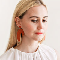 2: Model wears rust colored arced earrings and white blouse.