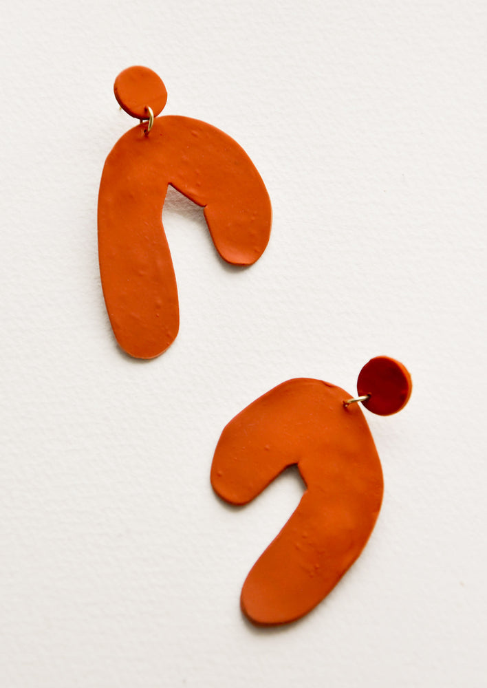 1: Drop earrings of rust colored clay in a flattened arc sharp.
