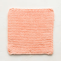 Papaya: A square, chunky knit cotton potholder in papaya pink.