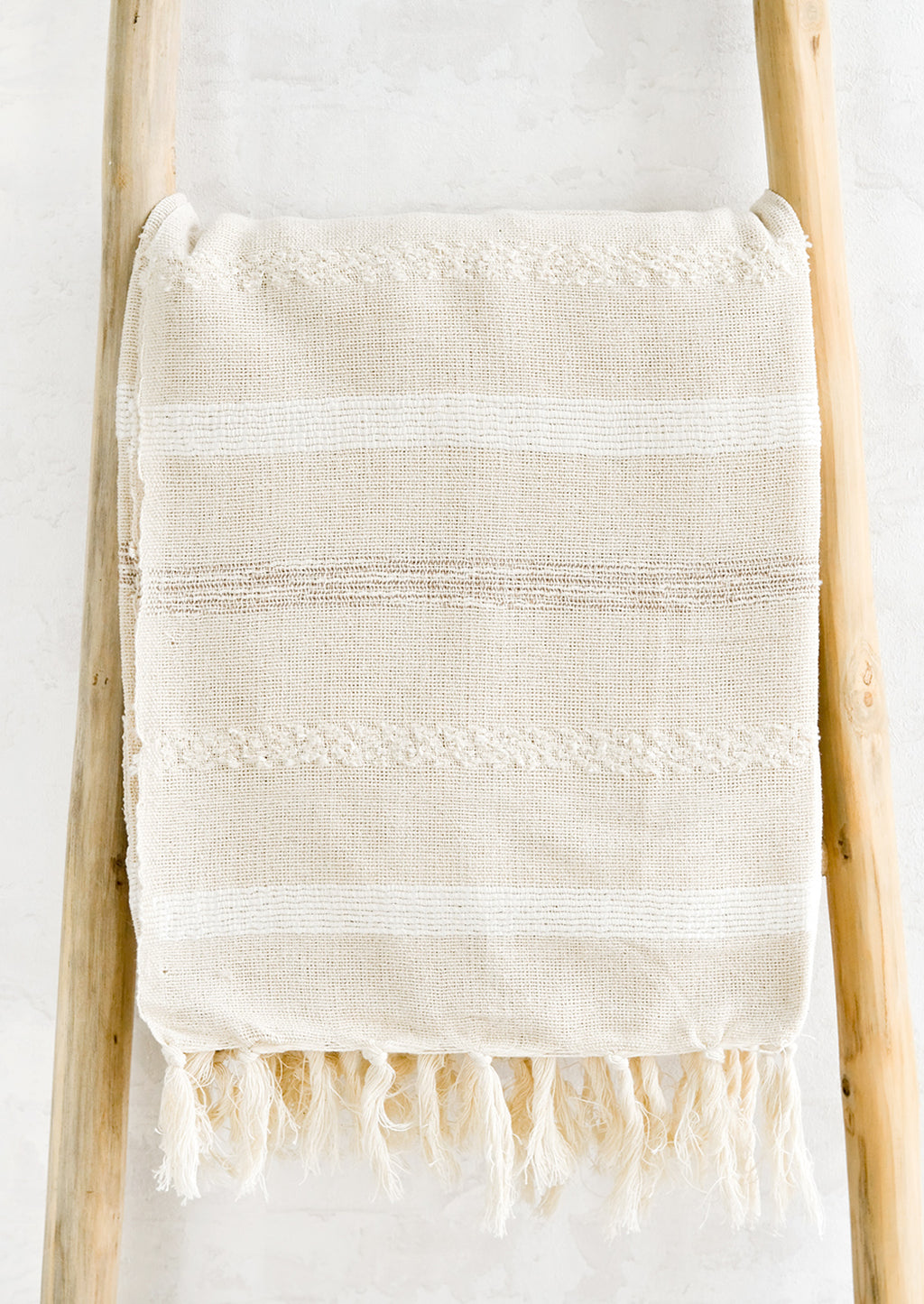 White Multi: A woven cotton gauze blanket with textured stripes in white on a display ladder.