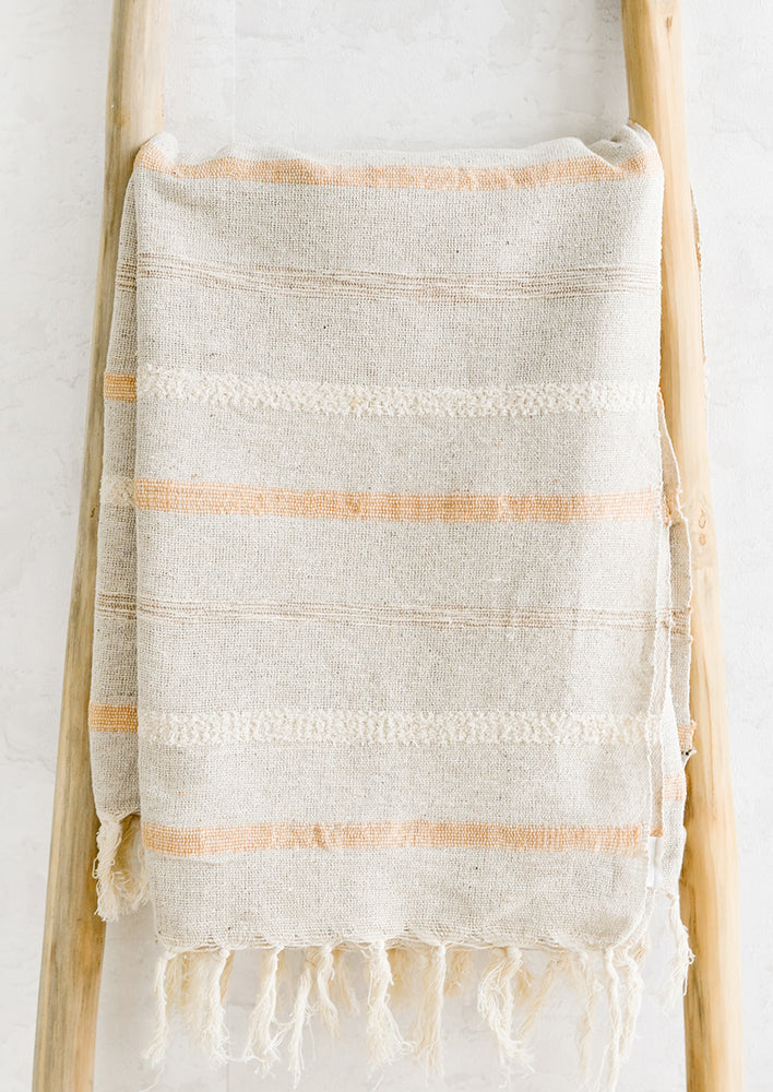 Apricot Multi: A woven cotton gauze blanket with textured stripes in apricot on a display ladder.