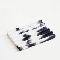 Black / White: A marbled black and white smooth concrete soap dish with troughs and ridges.