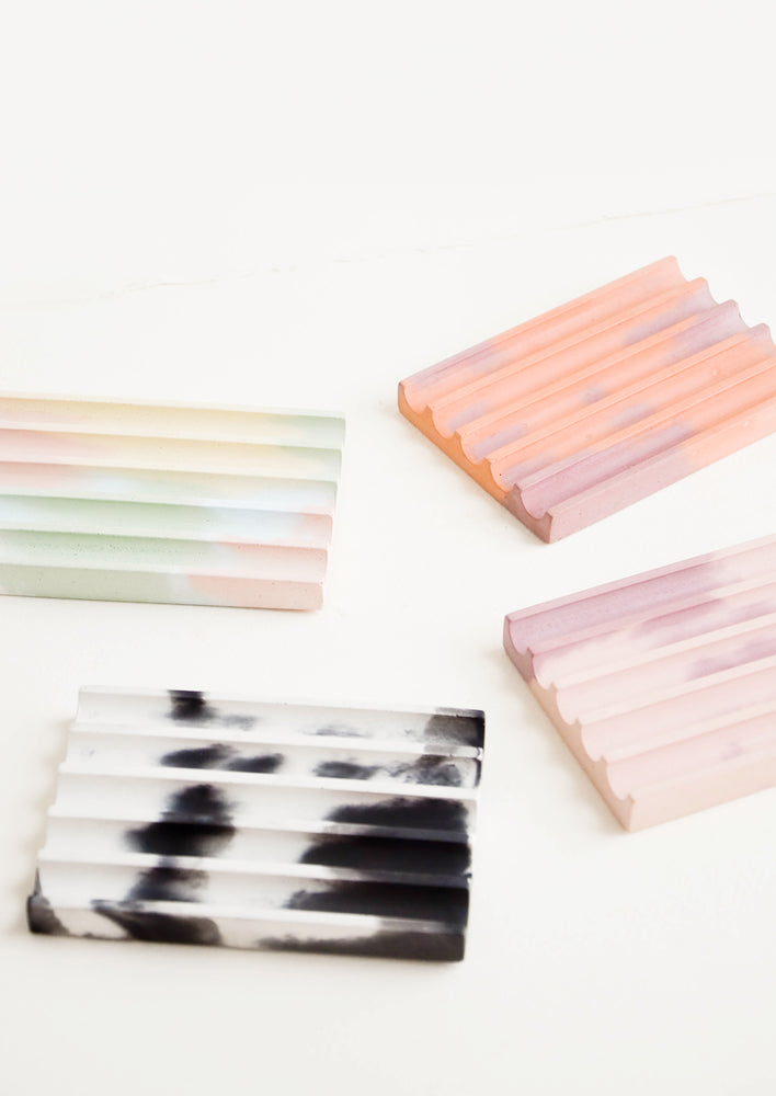 2: Four smooth concrete ridged soap dishes in rainbow, coral, pink, and black and white.