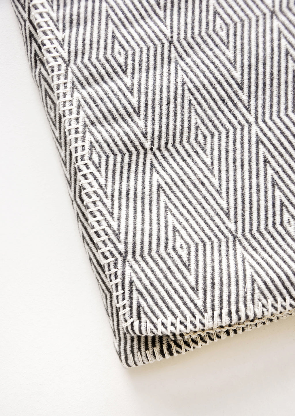 2: Cotton blanket with allover geometric diamond pattern in black and white, with whipstitched trim