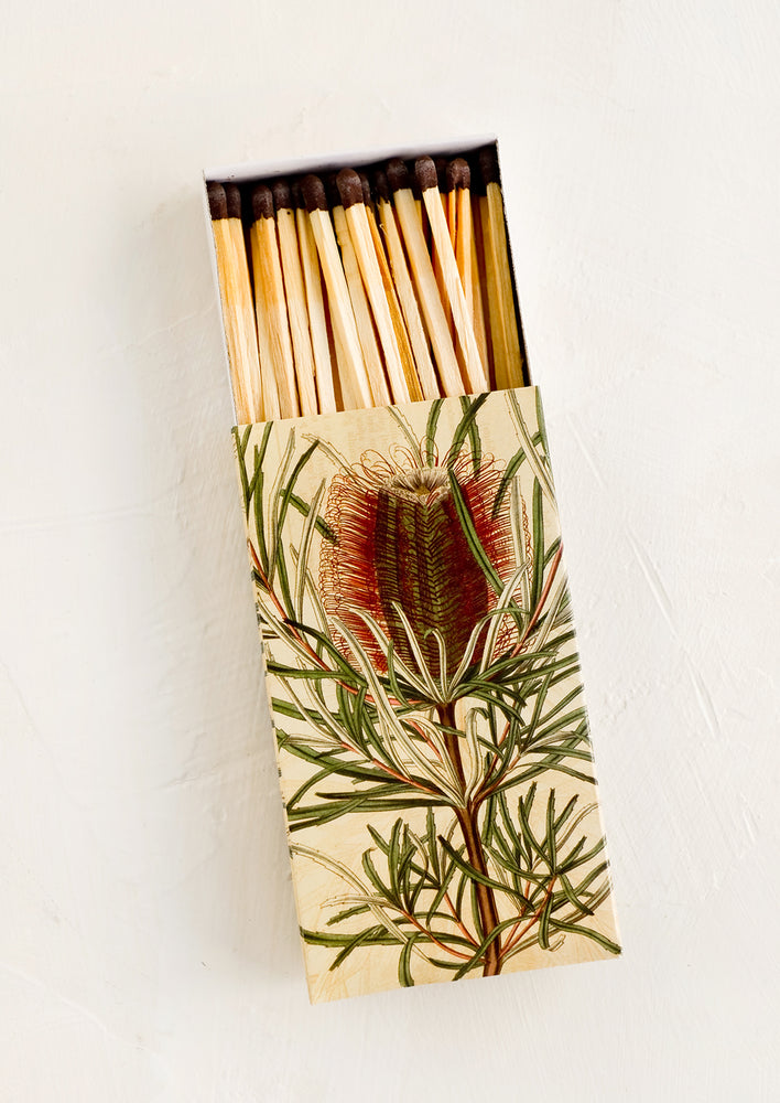 2: A matchbox with botanical protea print and brown-tipped long matches.