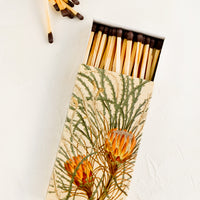 1: A matchbox with botanical protea print and brown-tipped long matches.