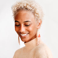 2: Model wears peach and orange fringe beaded earrings and peach colored sweater.