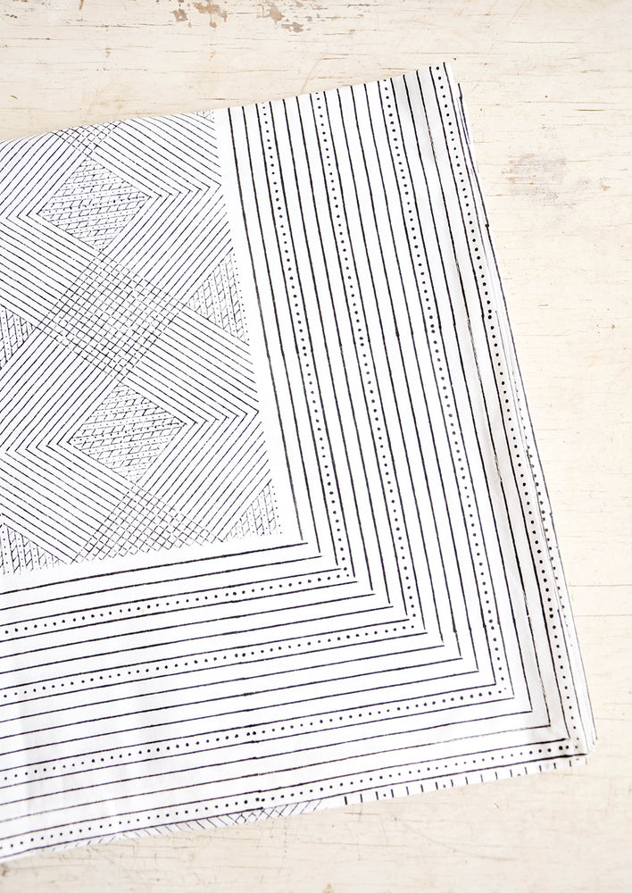 1: Black and white cotton tablecloth with geometric line and diamond print, displayed folded