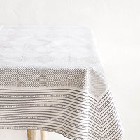 2: Black and white cotton tablecloth with geometric line and diamond print, displayed on a table