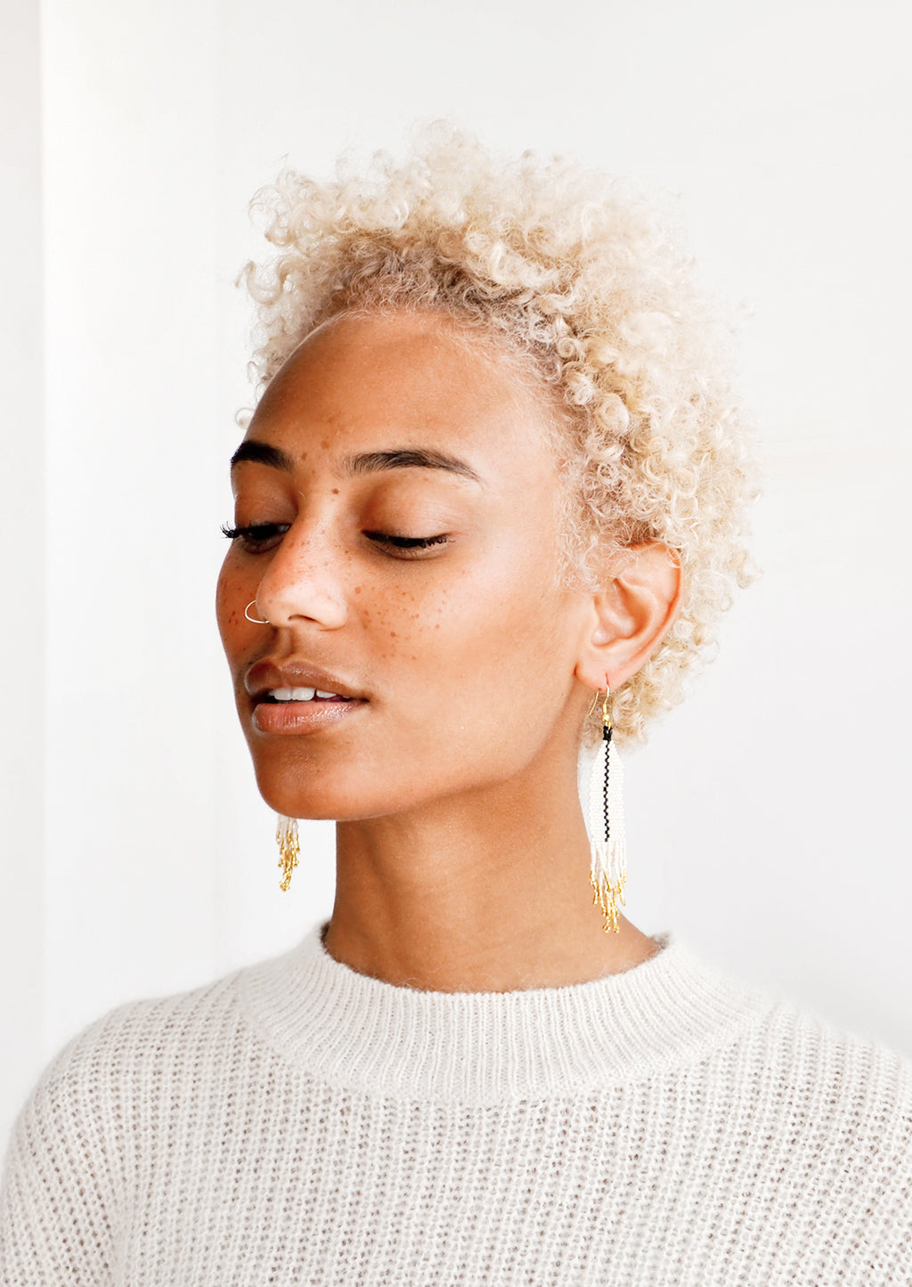 3: Model shot featuring woman wearing earrings and white top.